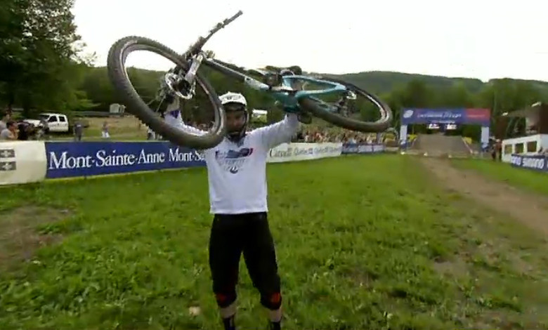 A victorious Jared Graves hoists his bike at the finish line.