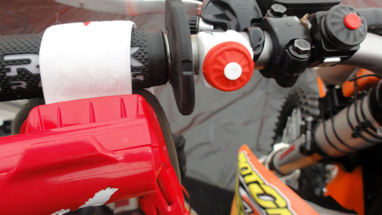 Pressing the handlebar mounted Speedbutton (shown here on a dirtbike) will wirelessly and instantly activate a motor to wind a new clear strip of film across your goggle.