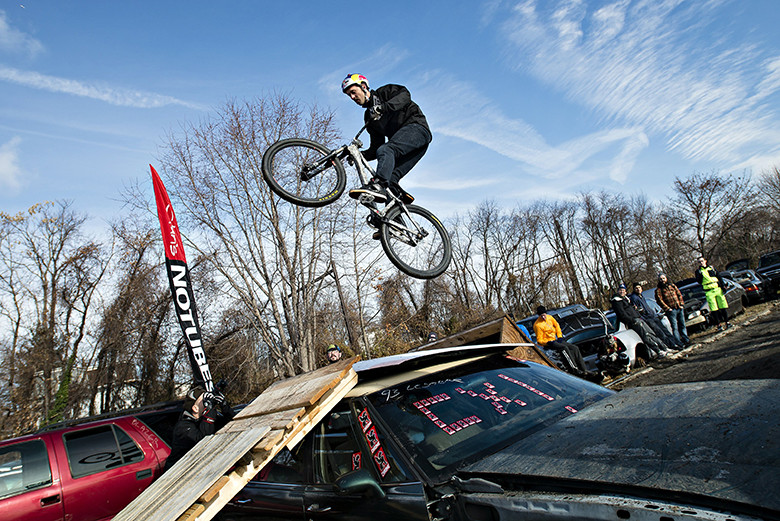 Aaron Chase jumps his bike over a car