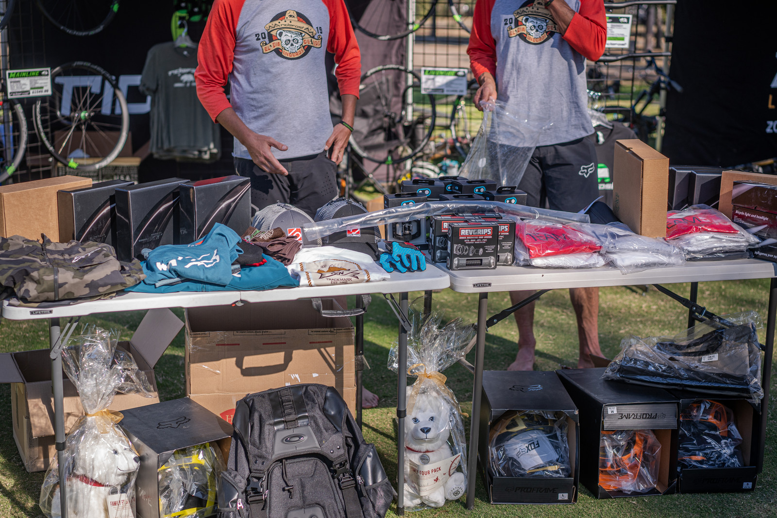 Showing off the 2019 Dia De Enduros shirt and the Raffle Table which included products from Crankbrothers, Five Ten, Rev Grips, Troy Lee Designs, Zodiac Lights, Hoppy Trails, Fox, Vital MTB, SkyPark, Oakley, Shimano, SDG Components, Fix Manufacturing, and RideFast Racing